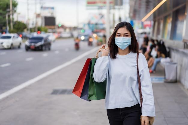Vrouw die de holdingssmartphone dragen van het gezichtsmasker en het winkelen zak die op bus wachten bij bushalte in stadsstraat