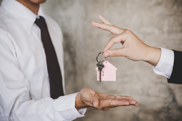 Vrouw die de huissleutels overhandigen aan een nieuw huis binnen lege grijze gekleurde ruimte.