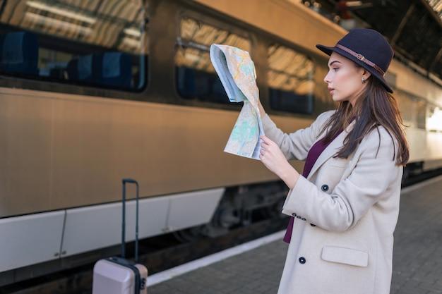 Vrouw die de kaart op het station bekijkt.