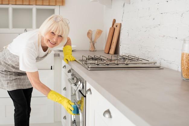 Vrouw die de keuken met handschoenen schoonmaakt
