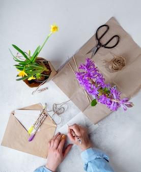 Vrouw die de lente ingemaakte bloemen inpakken als cadeau, ansichtkaarten schrijven. bovenaanzicht, portretoriëntatie
