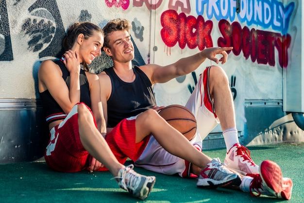 Vrouw die de man bekijkt die met fijner holdingsbasketbal richt