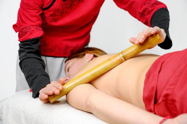 Vrouw die de massage van de bamboestok hebben in day spa.