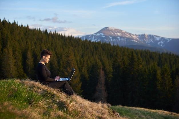 Vrouw die de mening inneemt terwijl het zitten met haar laptop bovenop een heuvel