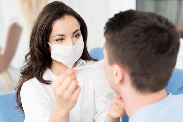 Vrouw die de mens helpt gezichtsmasker zetten