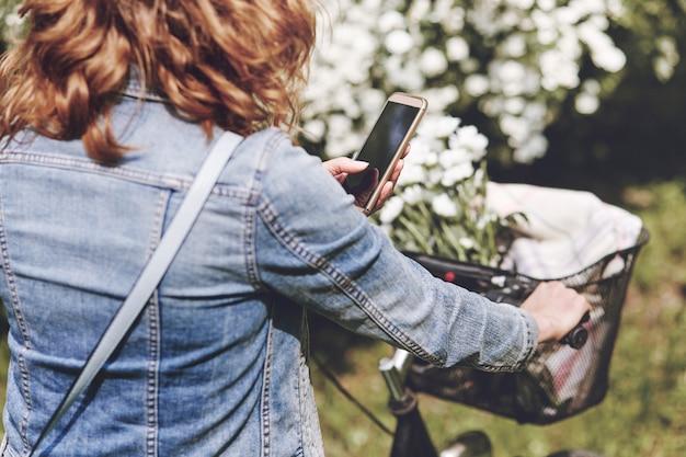 Vrouw die de mobiele telefoon gebruikt tijdens het fietsen