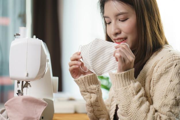 Vrouw die de naaimachine gebruikt om het gezichtsmasker te naaien tijdens de coronavirus pandemie.