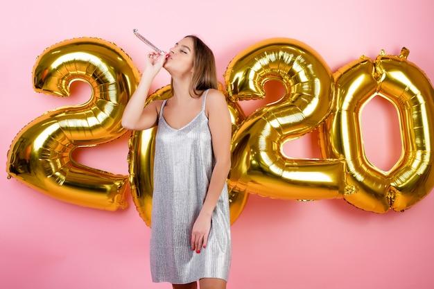 Vrouw die de nieuwe pijp van jaar blazende die kerstmis met 2020 ballons vieren over roze worden geïsoleerd