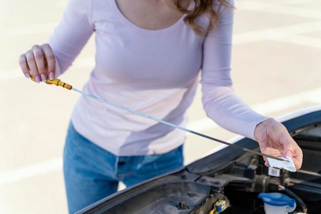Vrouw die de olie van haar auto controleert