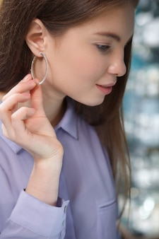 Vrouw die de oorring van de diamantring draagt