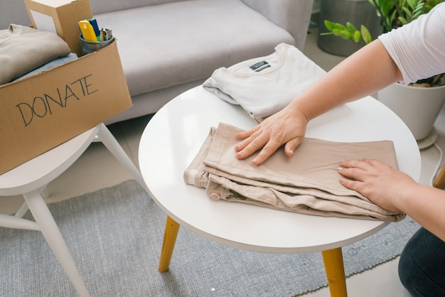 Vrouw die de oude kleren klaarmaakt die ze wil doneren voor een goed doel.