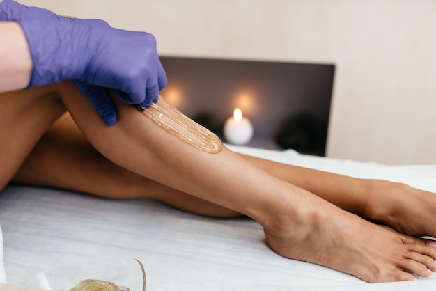 Vrouw die de procedure van de haarverwijdering op been met suikerhoudend deeg hebben