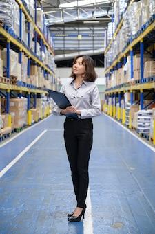 Vrouw die de producten in de plank bij de grote opslag en het magazijn controleert en telt
