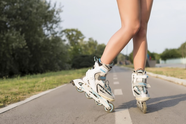Vrouw die de rolschaatsen draagt en op de grond staat