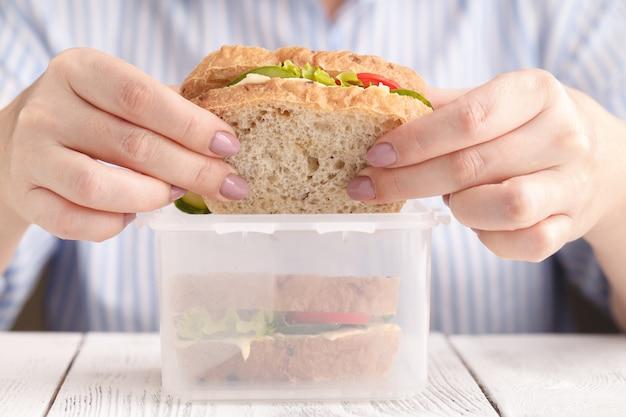 Vrouw die de sandwich van zalmpanini met tomaten en kaas eten op het werk