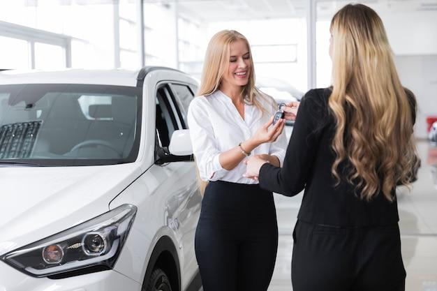 Vrouw die de sleutel van de nieuwe auto ontvangt