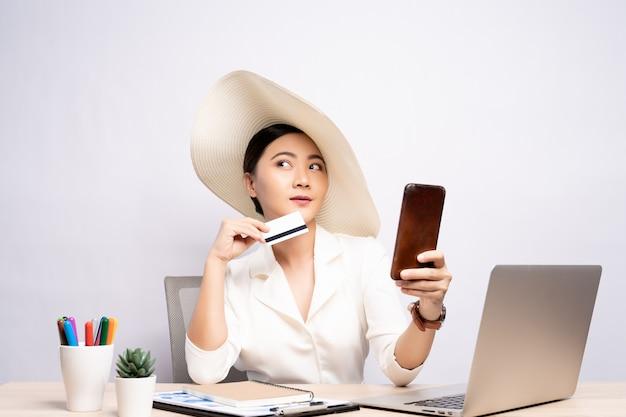 Vrouw die de slimme telefoon en creditcard van het hoedengebruik dragen op kantoor dat over achtergrond wordt geïsoleerd
