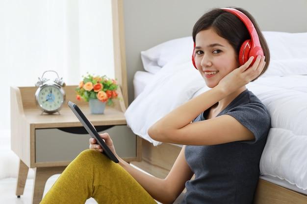 Vrouw die de tablet van de hoofdtelefoonholding draagt.