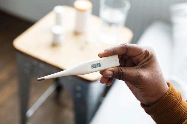 Vrouw die de temperatuur van haar vriend op een thermometer bekijkt