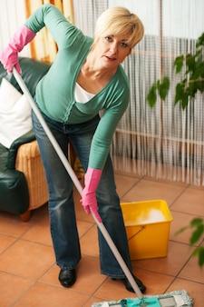 Vrouw die de vloer in haar huis dweilt