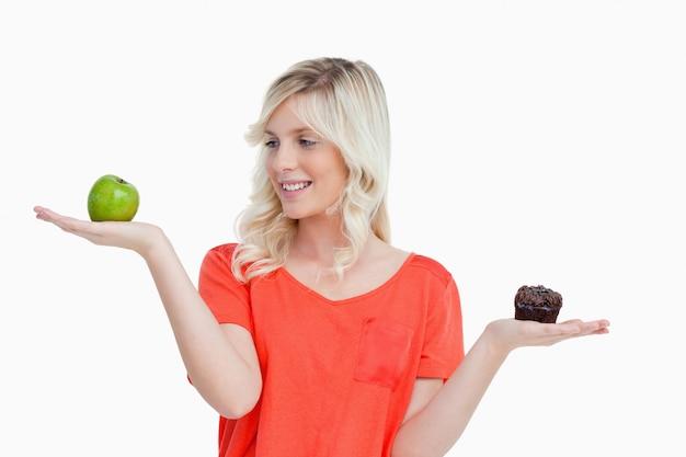 Vrouw die de voedselbalans imiteert om te kiezen tussen een appel en een muffin