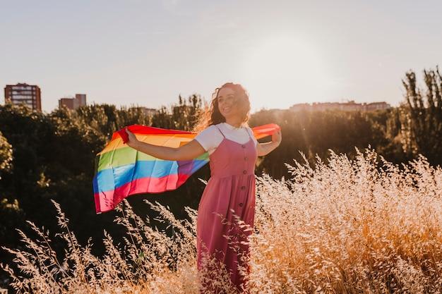 Vrouw die de vrolijke regenboogvlag houdt bij zonsondergang. geluk, vrijheid en liefde concept voor paren van hetzelfde geslacht. levensstijl buitenshuis