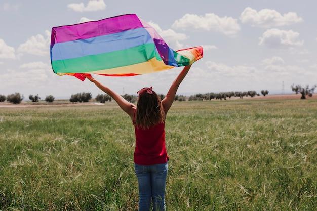 Vrouw die de vrolijke regenboogvlag op een groene weide in openlucht houdt. geluk, vrijheid en liefde concept voor paren van hetzelfde geslacht. levensstijl buitenshuis