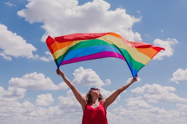Vrouw die de vrolijke regenboogvlag over blauwe en bewolkte hemel in openlucht houdt. geluk, vrijheid en liefde concept voor paren van hetzelfde geslacht. levensstijl buitenshuis
