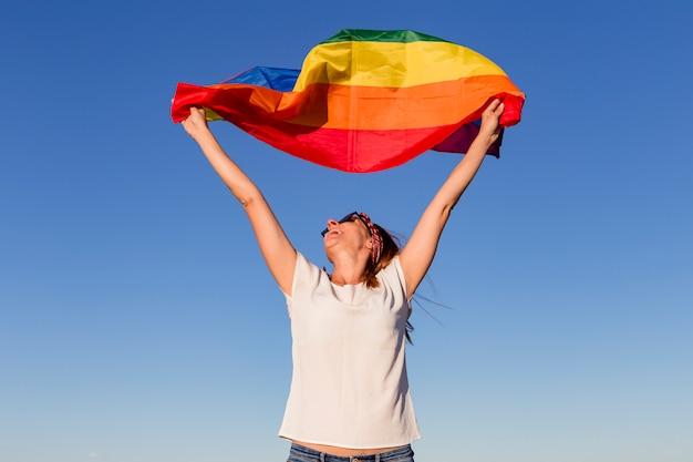 Vrouw die de vrolijke regenboogvlag over blauwe hemel in openlucht houdt.