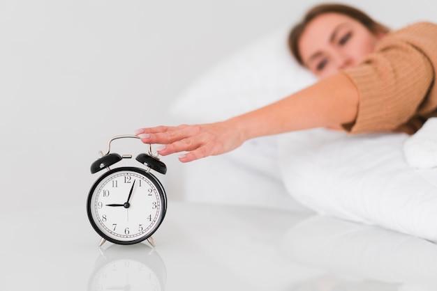 Vrouw die de wekker tegenhoudt