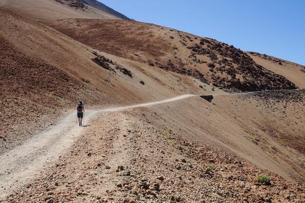 Vrouw die de witte bergweg beklimt aan teide, tenerife.