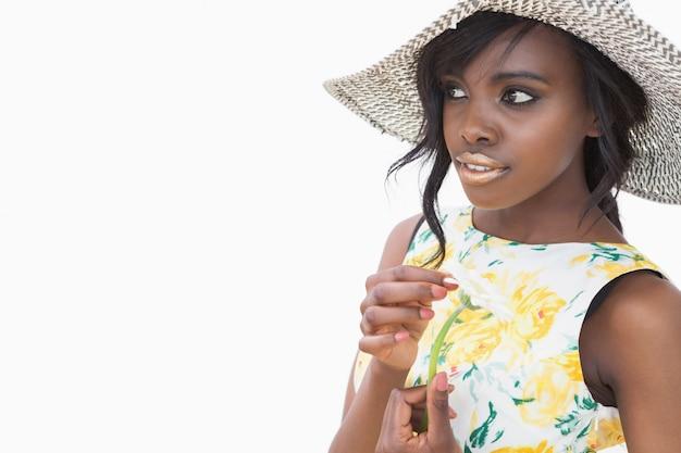 Vrouw die de zomerhoed draagt en madeliefje houdt