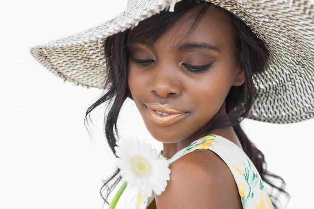 Vrouw die de zomerhoed draagt en witte bloem houdt