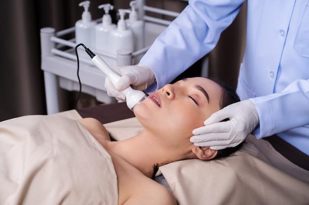 Vrouw die de zorg van de de behandelingshuid van de echografie gezichtsschoonheid ontvangt