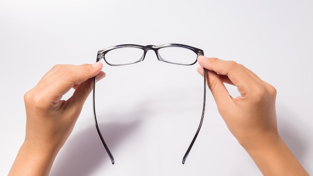 Vrouw die de zwarte bril van oogglazen met glanzend zwart frame houdt dat op wit wordt geïsoleerd