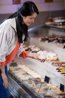 Vrouw die dessert van vertoning selecteert