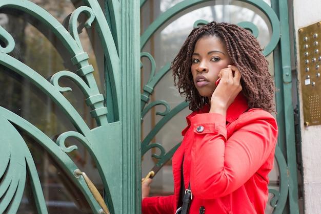 Vrouw die deur opent en door smartphone spreekt