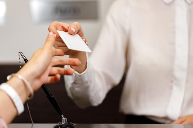 Vrouw die deursleutel ontvangt bij de receptie van het hotel close-up