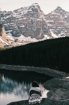 Vrouw die dichtbij het moraine-meer zit en de besneeuwde bergen bewondert