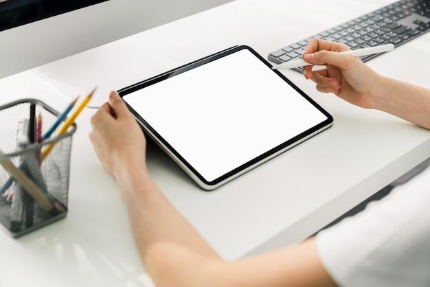 Vrouw die digitaal tabletmodel van het lege scherm en computer op het lijstbureau houden