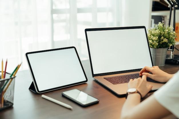 Vrouw die digitale laptop en tablet met smartphone op de lijst binnenshuis gebruiken. leeg scherm voor reclame