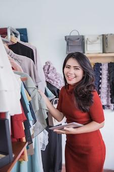 Vrouw die digitale tablet in kledingsopslag gebruiken
