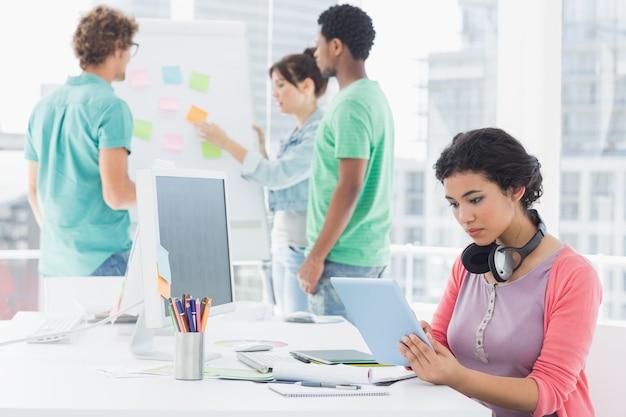 Vrouw die digitale tablet met erachter groep collega's gebruiken