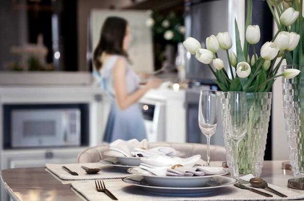 Vrouw die dishware op romantische dinerlijst voorbereidt