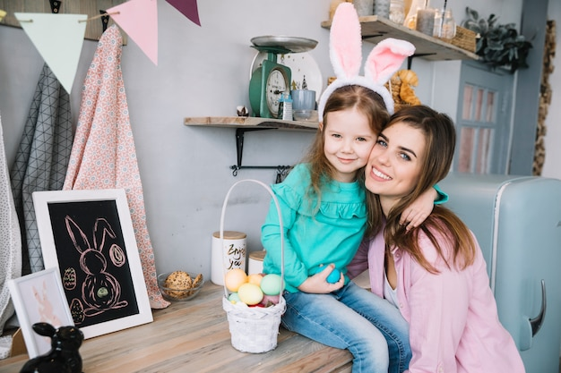 Vrouw die dochter in konijntjesoren koestert