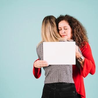 Vrouw die dochter omhelst en document blad houdt