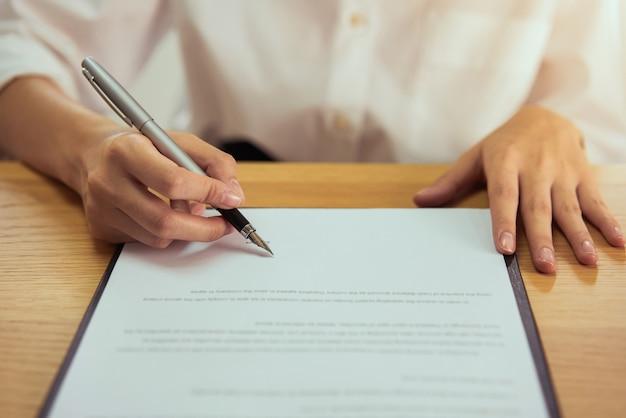 Vrouw die document en de pen van de handholding ondertekenen die handtekening zetten op papier, om hun rechten te machtigen.