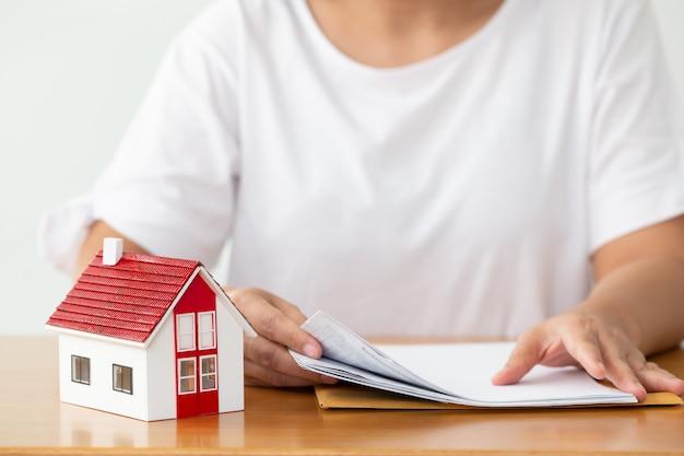 Vrouw die documentendossier voor leningshuis en herfinanciering voorbereidt