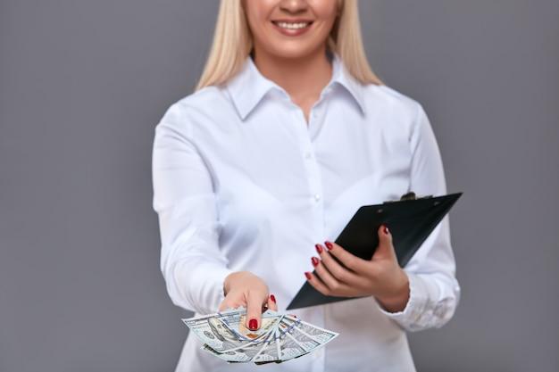 Vrouw die dollarscontant geld geven bij camera voor vragenlijst.
