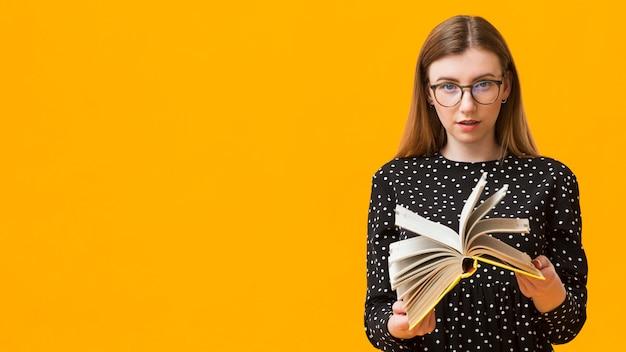 Vrouw die door boek kijkt